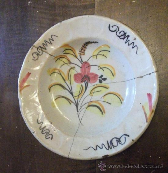 PLATO DE CERÁMICA O LOZA DE MANISES, MEDIADOS S. XIX CON FLOR DE COLORES, GRAPAS ORIGINALES (Antigüedades - Porcelanas y Cerámicas - Manises)