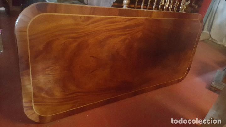 Mesa de comedor de madera con tablero haciendo aguas.