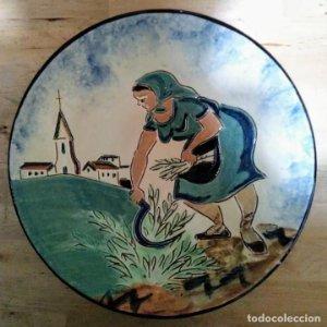 Plato de 32 cm de diámetro. 6 cm de alto con inscripción en dorso. Mujer con hoz segando trigo