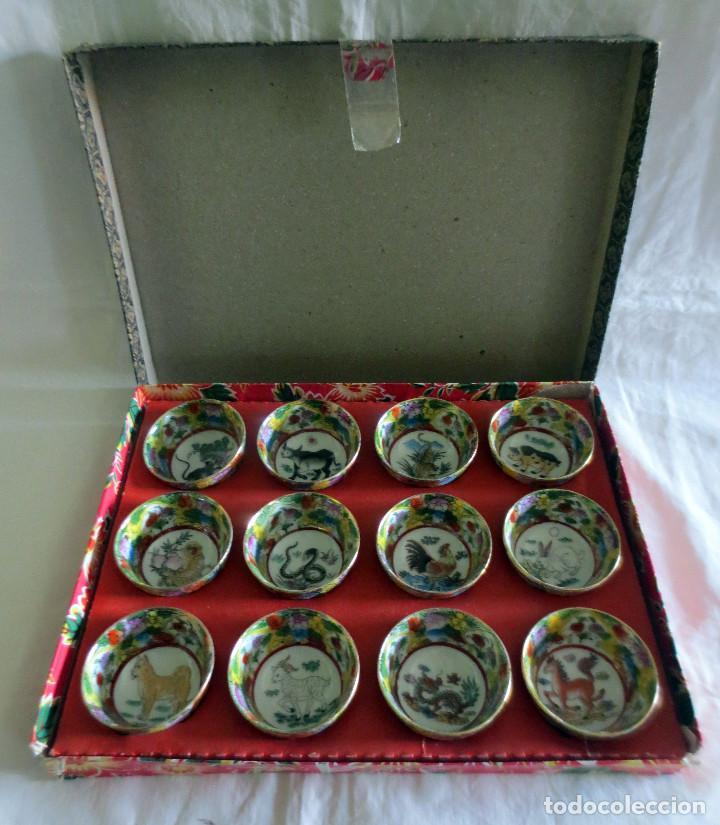 CAJA CON 12 VASOS DE SAKE EN PORCELANA CON FILO DE ORO EN EL BORDE E IMAGENES DEL AÑO CHINO (Antigüedades - Porcelanas y Cerámicas - China)