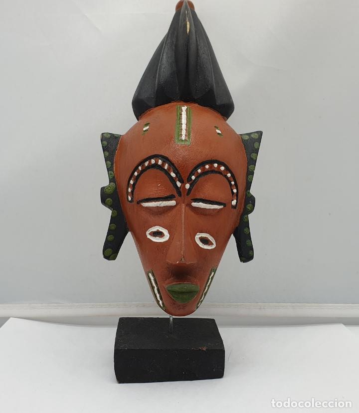 ESCULTURA DE MASCARA EN MADERA TALLADA Y DECORADA A MANO SOBRE PEANA . (Arte - Étnico - África)