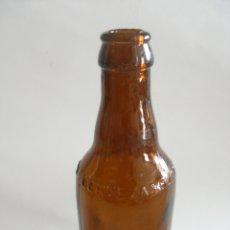 Botellas antiguas: BOTELLÍN COLOR AMBAR LETRAS EN RELIEVE CERVEZA EL LEÓN SAN SEBASTIÁN. Lote 179005552