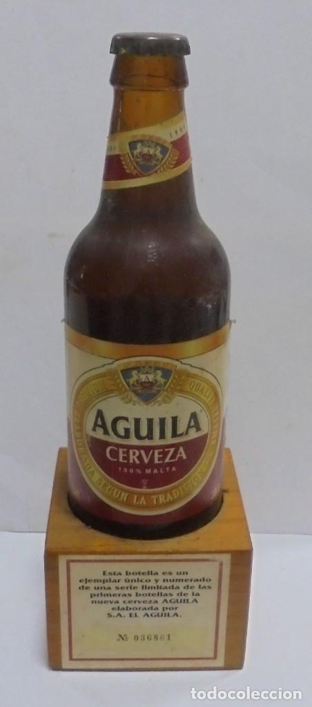 CERVEZA. AGUILA. EJEMPLAR UNICO Y ENUMERADO. PRIMERAS BOTELLAS. Nº 036861. EN PIE DE MADERA. VER (Coleccionismo - Botellas y Bebidas - Cerveza )