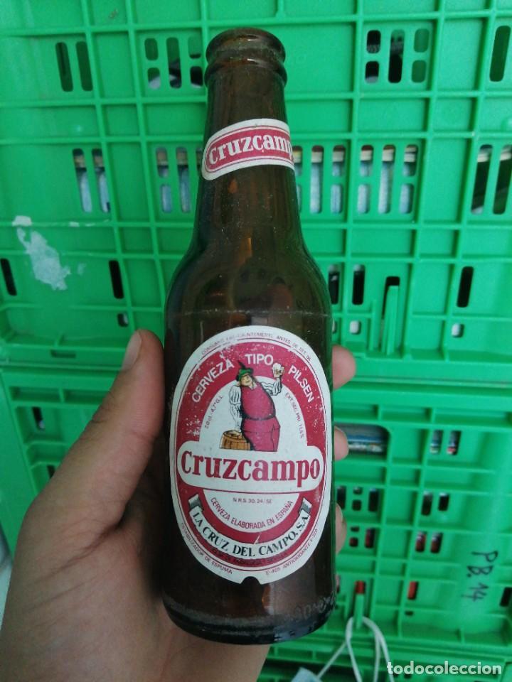BOTELLA DE CERVEZA LA CRUZ DEL CAMPO CRUZCAMPO ETIQUETA FABRICA DE SEVILLA TERCIO Y QUINTO (Coleccionismo - Botellas y Bebidas - Cerveza )