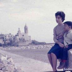 Fotografía antigua: SITGES. FOTO DE PLAYA. IGLESIA. MADRE E HIJO. INVIERNO DE 1956. DIAPOSITIVA ILFORD. Lote 277182668