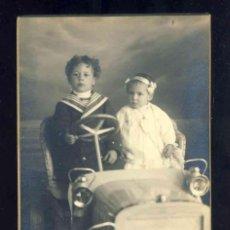Fotografía antigua: FOTO POSTAL: NIÑOS MONTADOS EN UN COCHE DE JUGUETE. FOTOGRAFO J.ALONSO. CARTON GRUESO. Lote 172073134