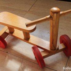 Antiguo triciclo de cuatro ruedas para bebe hecho en madera con ruedas de plástico duro. En uso.