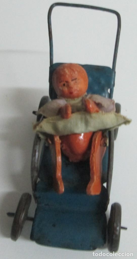 Juguetes antiguos de hojalata: Antigua sillita en hojalta engrapada con un pequeño bebe de molde en pasta - Foto 2 - 194404300