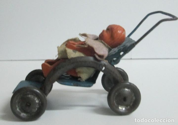 Juguetes antiguos de hojalata: Antigua sillita en hojalta engrapada con un pequeño bebe de molde en pasta - Foto 3 - 194404300