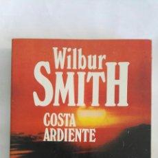 Libros de segunda mano: COSTA ARDIENTE WILBUR SMITH. Lote 168494226
