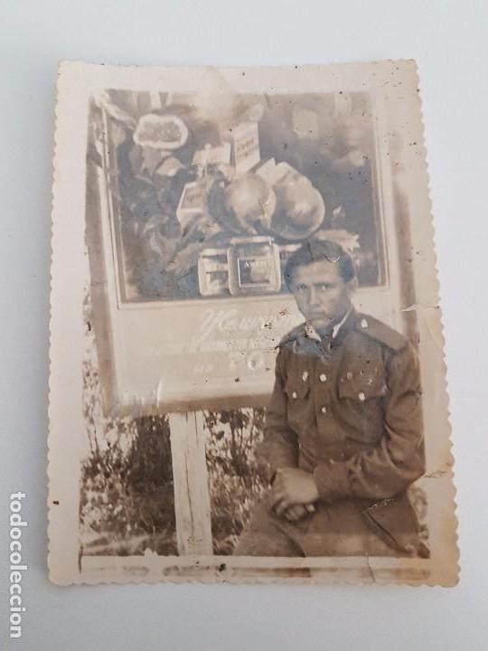 FOTOGRAFÍA SOLDADO RUSO JUNTO A ANUNCIO PUBLICITARIO (Militar - Fotografía Militar - II Guerra Mundial)